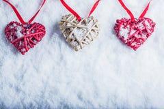 Trois beaux coeurs romantiques de vintage accrochent sur une bande rouge sur un fond blanc de neige Amour et concept de jour de v Image stock