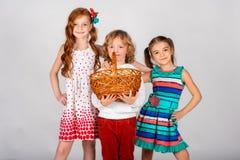 Trois beaux enfants sur un fond blanc, le garçon tient un panier avec image libre de droits