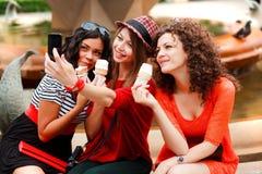 Trois beaux femmes se photographiant Images stock