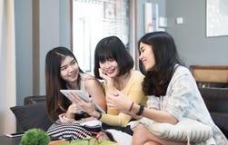 Trois beaux jeunes amis asiatiques de femmes employant le sourire parlant de tablette et riant ensemble Images libres de droits