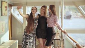 Trois beaux modèles faisant le selfie au téléphone portable se tenant à l'intérieur du bateau clips vidéos