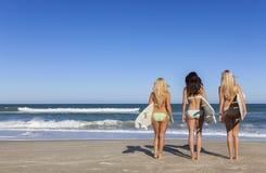 Trois beaux surfers de femmes dans des bikinis avec des planches de surf chez Beac Photo stock