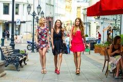 Trois belles amies de jeunes femmes marchent sur une rue d'été Photo stock