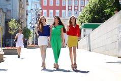 Trois belles amies de jeunes femmes marchent sur une rue d'été Photos libres de droits