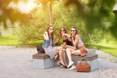 Trois belles amies mangent la crème glacée, posant sous l'arbre Image libre de droits