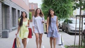 Trois belles amies vont le long de la rue avec des paquets après l'achat et parlent les uns avec les autres Mouvement lent HD clips vidéos