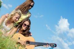 Trois belles femmes heureuses chantant et jouant la guitare contre le ciel bleu Images stock
