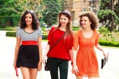 Trois belles femmes marchant sur la rue ensoleillée Photo stock