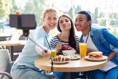 Trois belles femmes posant tout en prenant des selfies en café Images stock