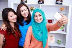 Trois belles femmes prenant des photos avec l'appareil-photo de smartphone Photographie stock