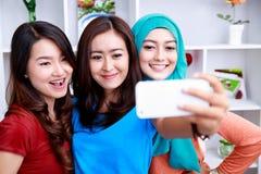 Trois belles femmes prenant des photos avec l'appareil-photo de smartphone Photo stock