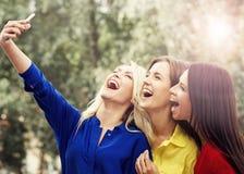 Trois belles femmes prenant des selfies avec un smartphone Photo libre de droits