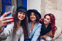 Trois belles femmes prenant le selfie sur la rue de ville Amis accrochant et ayant l'amusement Image stock