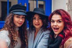 Trois belles femmes prenant le selfie sur la rue de ville Amis accrochant et ayant l'amusement Photographie stock libre de droits