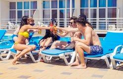 Trois belles filles buvant des cocktails près de la piscine Photographie stock