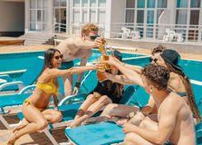 Trois belles filles buvant des cocktails près de la piscine Photographie stock libre de droits