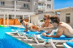 Trois belles filles buvant des cocktails près de la piscine Image stock