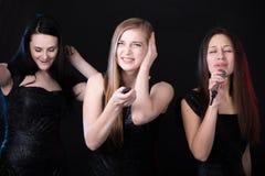 Trois belles filles dans le karaoke Photos stock
