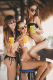 Trois belles filles dans une barre sur la plage Photographie stock