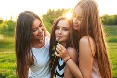 Trois belles filles marchant et riant sur le coucher du soleil en parc Concept d'amitié Photographie stock