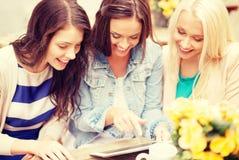 Trois belles filles regardant le PC de comprimé en café Images libres de droits