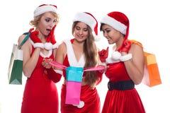 Trois belles filles sexy portant le père noël vêtx avec la boutique Photographie stock libre de droits