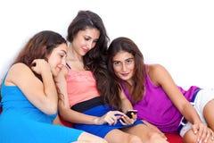 Trois belles jeunes amies ayant l'amusement avec le pho futé de cellules Images libres de droits