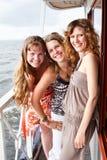 Trois belles jeunes femelles sur le paquet du bateau Image libre de droits
