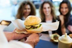 Trois belles jeunes femmes achetant des boulettes de viande sur un camion de nourriture Photographie stock libre de droits