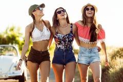 Trois belles jeunes femmes appréciant l'été sur le voyage par la route Photos stock