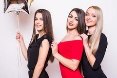 Trois belles jeunes femmes dans la nuit s'habille sur le côté et tenir les ballons en forme d'étoile au-dessus du blanc Image libre de droits