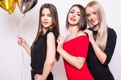 Trois belles jeunes femmes dans la nuit s'habille sur le côté et tenir les ballons en forme d'étoile au-dessus du blanc Photographie stock libre de droits
