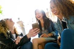 Trois belles jeunes femmes employant ils téléphone portable dans la rue Photos stock