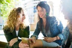 Trois belles jeunes femmes employant ils téléphone portable dans la rue Image stock