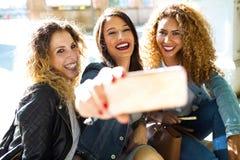 Trois belles jeunes femmes employant ils téléphone portable dans la rue Photo stock