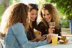 Trois belles jeunes femmes employant ils téléphone portable dans la rue Photographie stock
