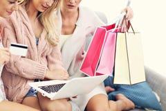 Trois belles jeunes femmes faisant des emplettes en ligne Image stock