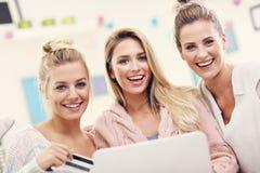 Trois belles jeunes femmes faisant des emplettes en ligne Photo stock