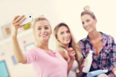 Trois belles jeunes femmes refroidissant à la maison et prenant le selfie Photos stock