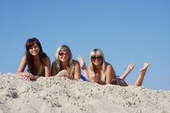 Trois belles jeunes femmes sur une sable-piqûre Image libre de droits