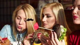 Trois belles jeunes filles avec le maquillage lumineux mangent des hamburgers dans un café banque de vidéos