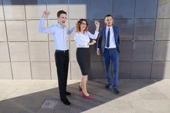 Trois belles personnes énergiques rient, se réjouissent le succès, souriant Images stock
