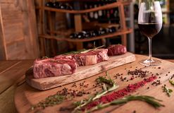 Trois biftecks de nervure AI sur une planche à découper en bois avec un brin de romarin, de grains de poivre colorés, de conserve photographie stock libre de droits