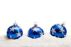 Trois billes bleues de Noël dans la neige - d'isolement images libres de droits