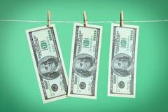 Trois billets de banque de 100 dollars sèche sur une corde Photos stock