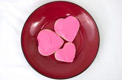 Trois biscuits en forme de coeur disposés du plat rouge Photo libre de droits