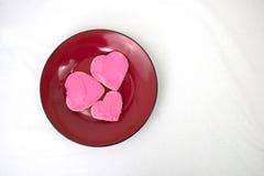 Trois biscuits en forme de coeur disposés du plat rouge Photos libres de droits