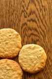 Trois biscuits faits maison de beurre d'arachide s'étendant sur une table rustique de chêne foncé photographie stock libre de droits