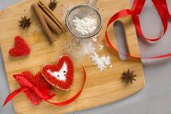Trois biscuits rouges de coeur avec le ruban, un arc, la farine et la cannelle sur le fond en bois Fabriqué à la main avec amour, Photo stock