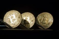 Trois bitcoins d'or avec des fourchettes Photographie stock